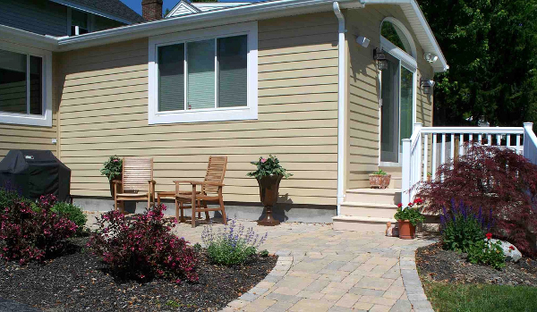 Acting as a buffer between the driveway and deck, the paver patio blends well between the colors of the house, deck and colorful landscaping. The patio provides a nice seating area as well as a pathway between the driveway and side stair to the rear deck.