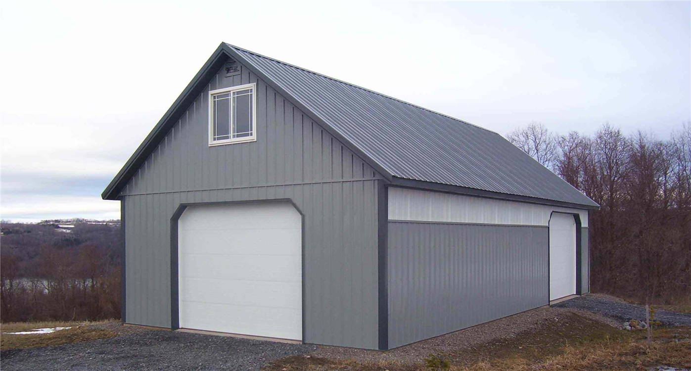 This 24'x48' pole barn features two overhead doors, an entry door, two large windows in the attic space and opaque panels along the sides of the building that allow light to pass into the barn.