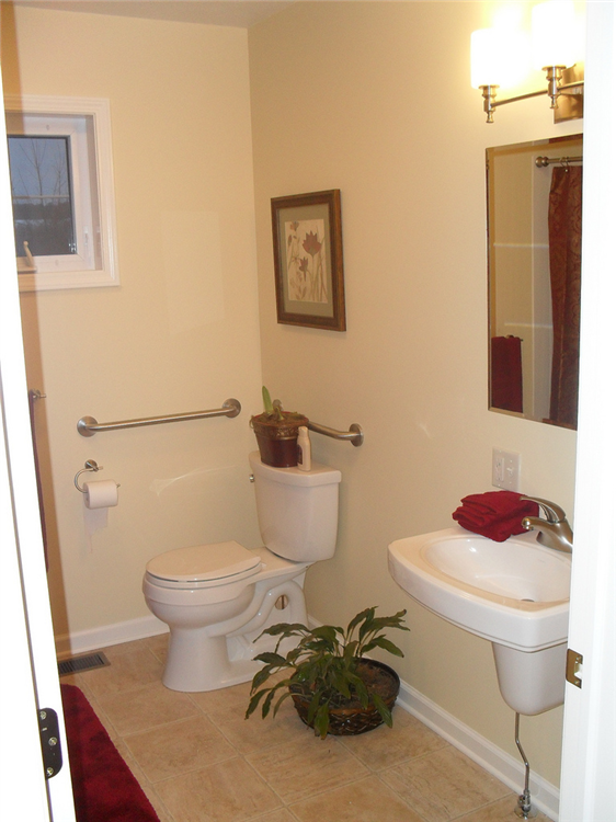 This bath features a wall hung sink and grab bars around the water closet.