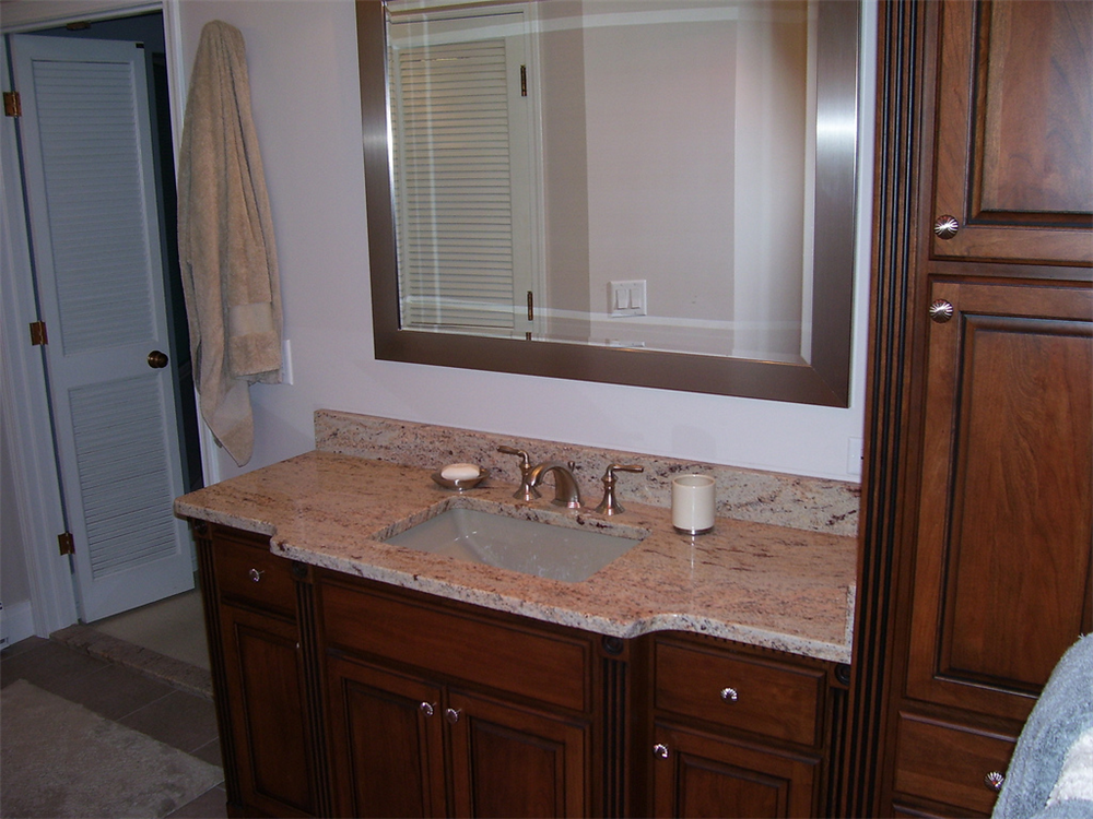 This cherry vanity cabinet has fluted columns and an extended counter in front of the sink.