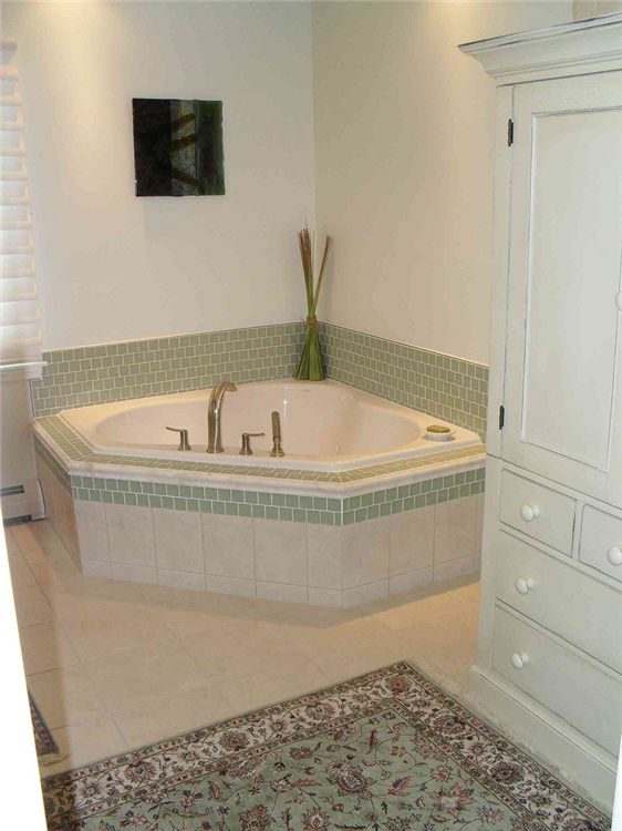 The whirlpool was relocated to the corner of the room freeing space for new cabinetry. The same glass tile used for the vanity was installed as the backsplash and face of the new whirlpool.