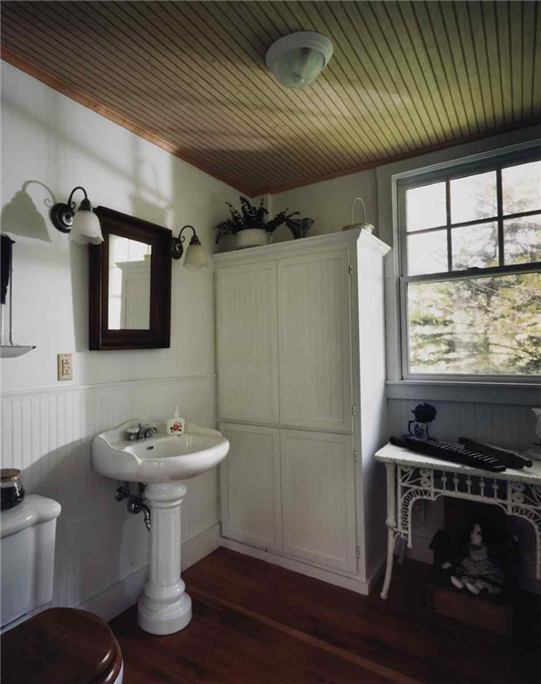 A combination of natural wood and white accents bring together elements of contemporary country design. The wood stained beadboard ceiling, white beadboard walls and hard wood flooring are the architectural elements of the room. A pedestal sink with matching toilet and wall sconces add interest.