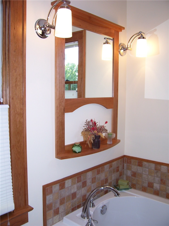 This custom mirror and shelf gave purpose to the new accent sconce lights for this new whirlpool tub.
