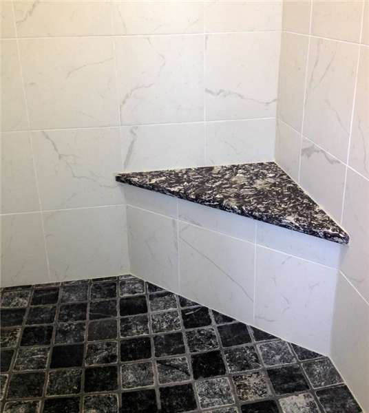 "The fiberglass stall was replaced with a custom-built shower complete with a corner shower seat and an inset wall niche for soaps and shampoos. Marble wall tile from Dobkin Tile (Elegance: Perseo Statuario) is accented by glass listello tile (Best Tile ""Precious Gems""), a Cambria ""Braemar"" shower seat and non-skid black tile floor (Dobkin ""Toros"" Black Tumbled Marble)."