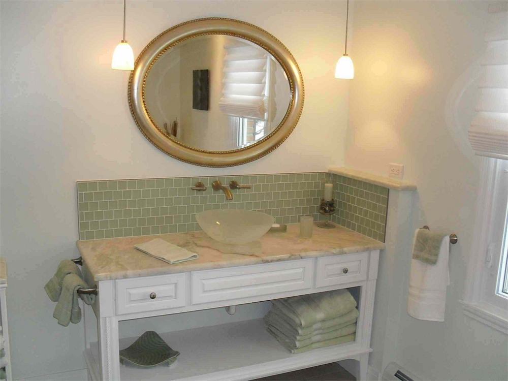 This unique vanity features a glass bowl sink with wall mount faucet set on a marble counter top. The vanity was designed to provide drawer storage for toiletries and shelf storage for towels.