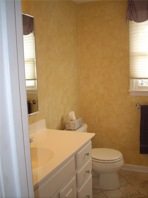 This bath makeover was kept simple by painting the existing cabinetry and adding some faux paint on the walls.