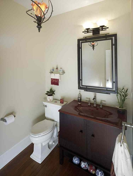 This Chinese-inspired bathroom features a red cast iron vanity top set on a custom crafted cabinet. Baths are a perfect setting for feng shui design. Feng shui translates to wind and water. Chinese aesthetics include the use of color, red, yellow and black. The home owner selected Asian accents for the mirror, towel rack and light fixture to complete the look.