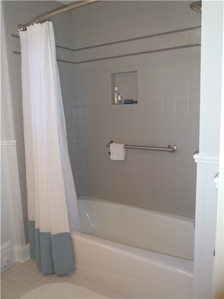The biggest change in the bath was the shower with its sleek tub, grey tiled walls, grab bar for safety and new plumbing fixtures. The walls of the bathroom are painted a dove grey to complement the tile.