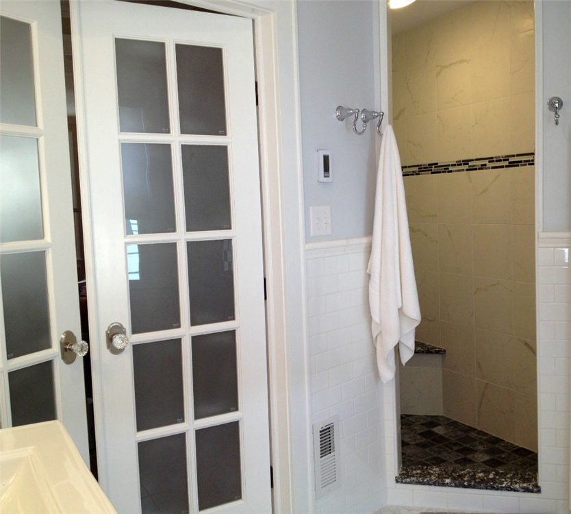 French doors in the bedroom serve as an entryway to the master bathroom and walk-in shower.