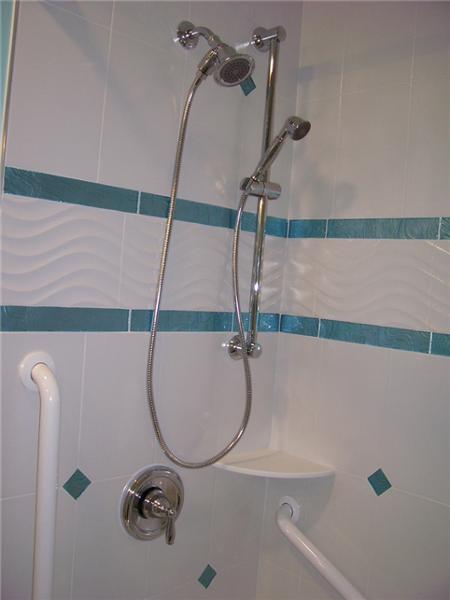 White wall grab bars makes it easy and safe for using the hand-held shower unit and for entering and exiting the tub.