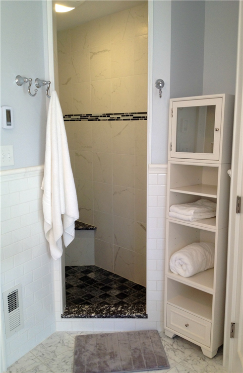 Open shelving provides storage for towels. The homeowners supplied the modular shelf unit.