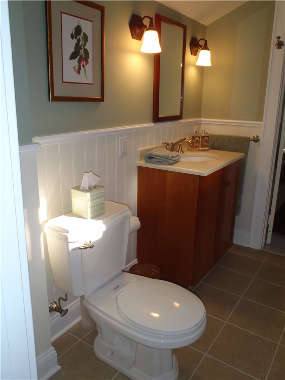 "The second floor bathroom has become a ""jewel"" with apple green painted walls and artwork to accent the sink, resurfaced vanity and wainscoted walls."