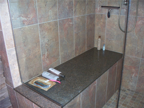 A large quartz shower seat was built-in to this custom tiled master bath shower.