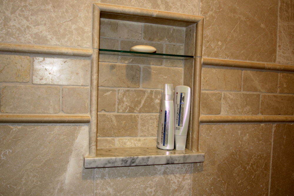 A beautifully designed inset wall niche provides a place for soap and shampoos. The glass shelf was added specifically for soaps and easy maintenance.