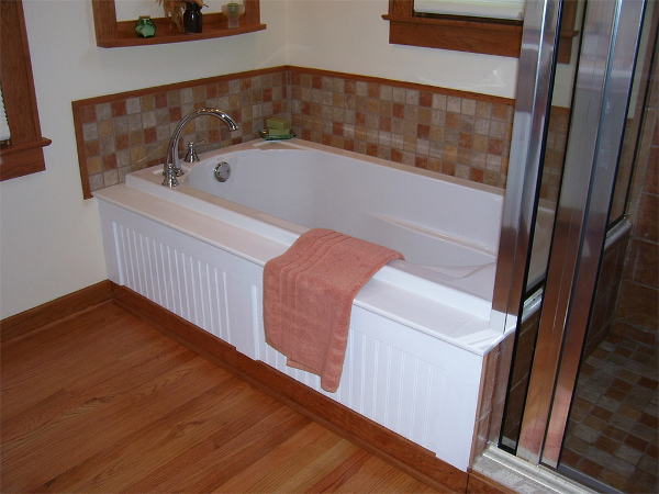 This soaking tub has a wood beadboard front and tile splash that ties into the attached custom tile shower.