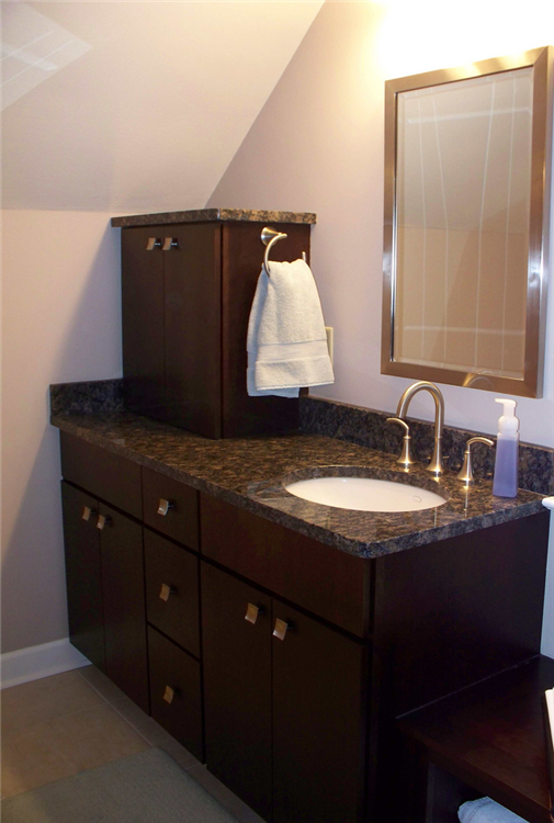 These cherry cabinets, granite top and brushed nickel fixtures create a new look for this bathroom. The new cabinets and drawer allow for added storage space.