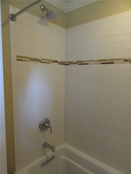The walls of this tub were tiled with the classic white subway tile and glass tile accent.