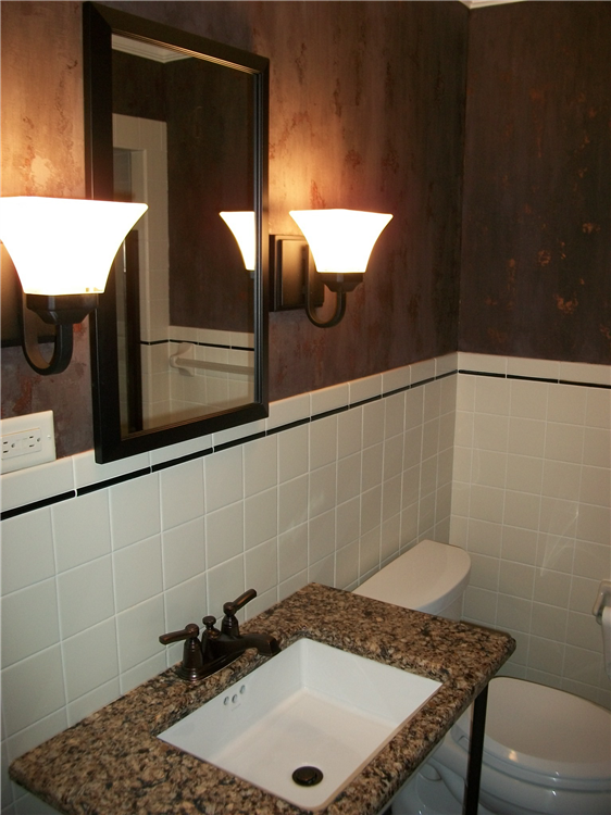 The white tile wainscot and dark based faux paint create a nice contrast in this new powder room.