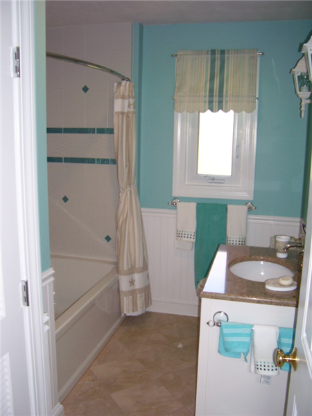 Turquoise wall color and tile accents with white wainscoting and window trim create an ocean look.