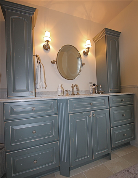 Rustic distressed slate-blue glazed cabinets with elegant arches and carvings were selected for the vanity. A Carerra marble countertop, oval mirror and matching shaded sconces add another elegant element to the room. Storage for towels and items for grooming is provided by the dual cabinets that flank the counter.