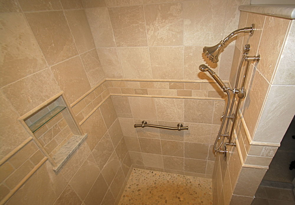 "The large walk-in shower is a ""room within a room"". Stunning details include the river rock floor tile that provides a non-slip surface for users. Matte finish marble tiles were selected for the interior. The border is 3"" by 6"" tile and listello accent tile. Carrera marble tops the wall and creates the lower edge of the wall niche."