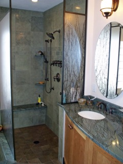 Granite tile and seating area with a hand-held shower unit and oversized shower head add to the luxury of this walk-in shower.