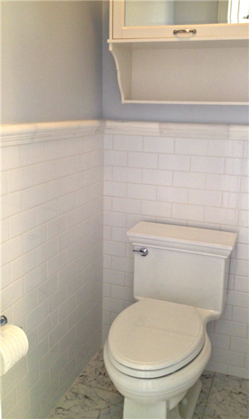 "The toilet area is framed by classic white 3""x6"" subway wall tile from Dobkin Tile and the chair rail is ""Dolomite White"" edging from Dobkin. The toilet is Kohler and a medicine cabinet placed above the toilet is from Nutone. Floor tile is Best Tile ""Elegance Venatino""."