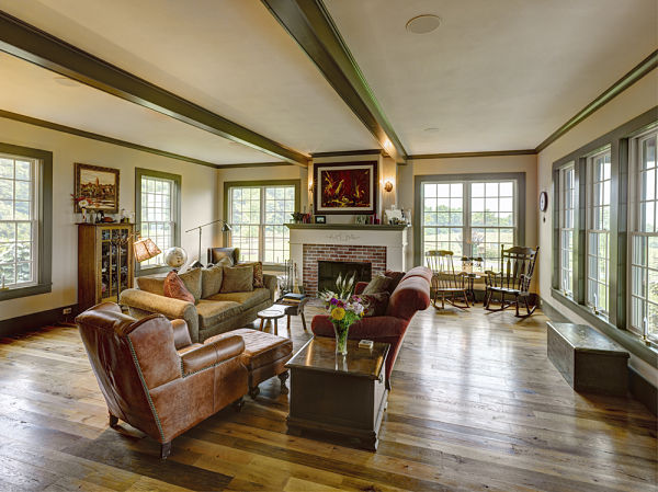 Farmhouse Living Room With Beamed Ceiling And Fireplace A Television Is Hidden Behind The Artwork