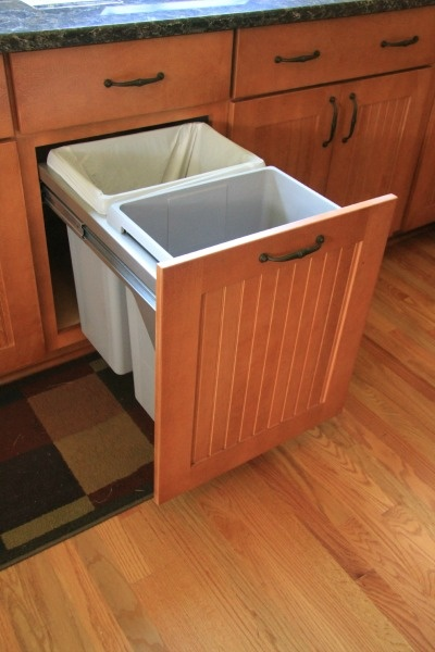 Pullout cabinet drawer with waste and recycling bins.