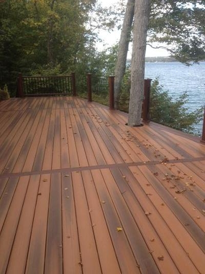 composite deck with tree cut-out, clear rail panels and lake view