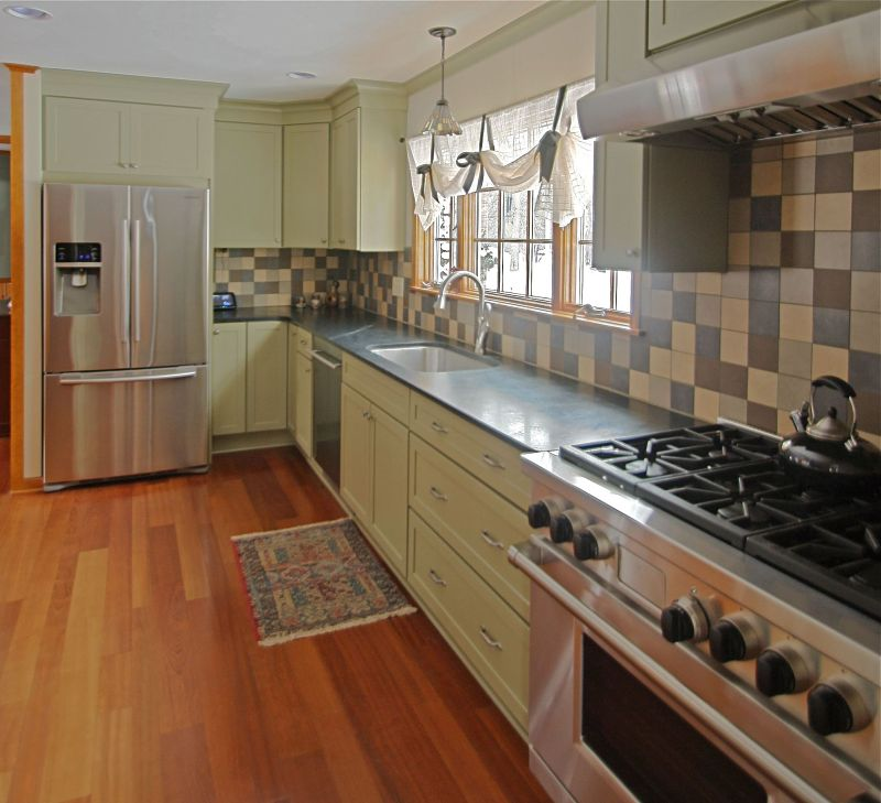 A Wolf range and hood, Asko dishwasher, Samsung French door refrigerator and under-mount stainless steel farm sink were selected for the kitchen. Note the length of the soapstone counter that provides ample space for preparing meals.