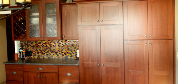 Cherry cabinets are used for a beverage center and tall pantry storage. The perimeter cabinets added ample storage to the home. Decorative glass doors were added.