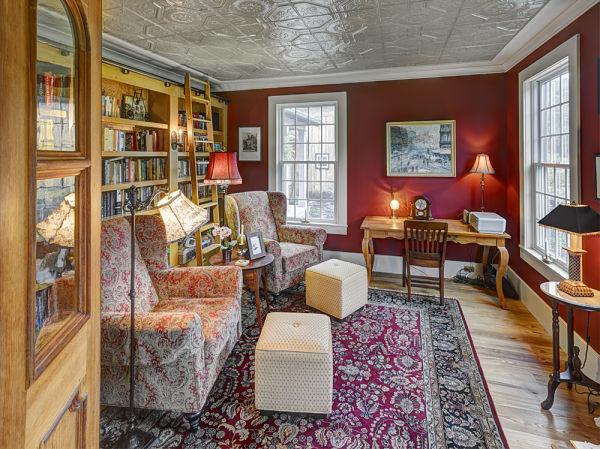 farmhouse library with custom bookshelves, ladder and tin ceiling