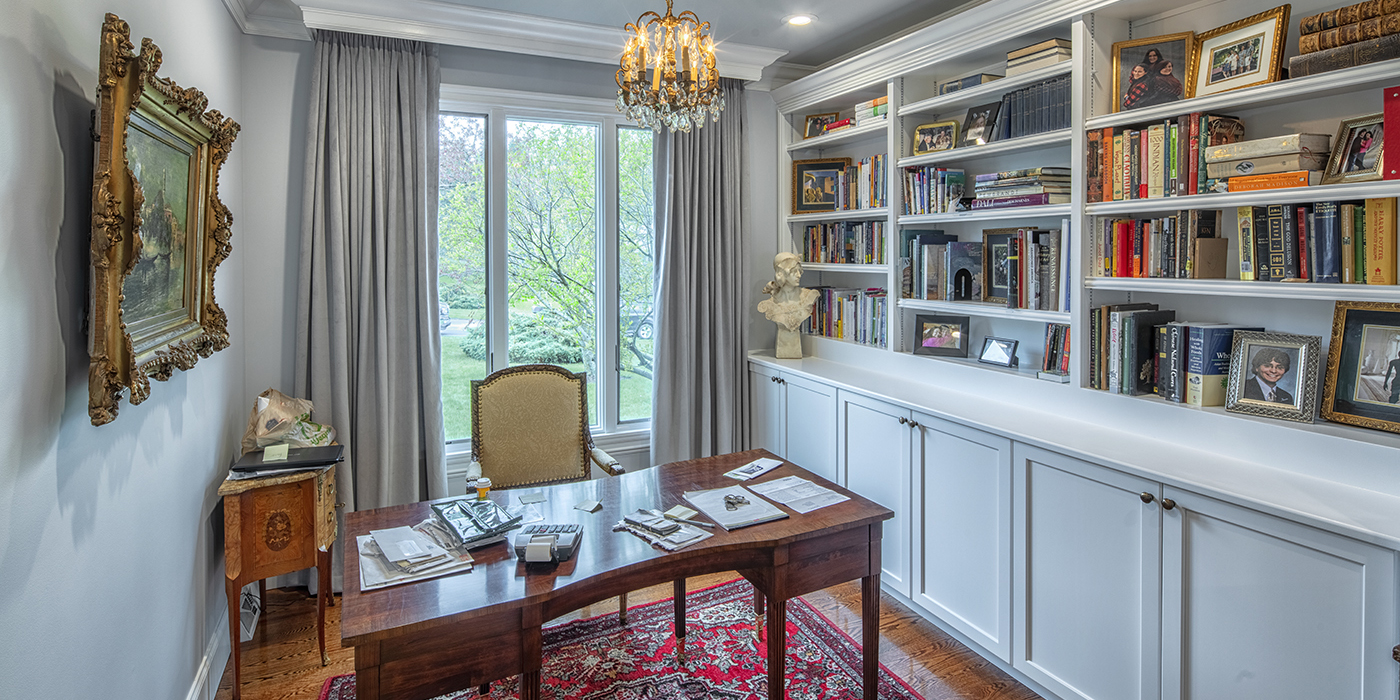 Home office with built-in bookcase, antique decor, and a large back window.