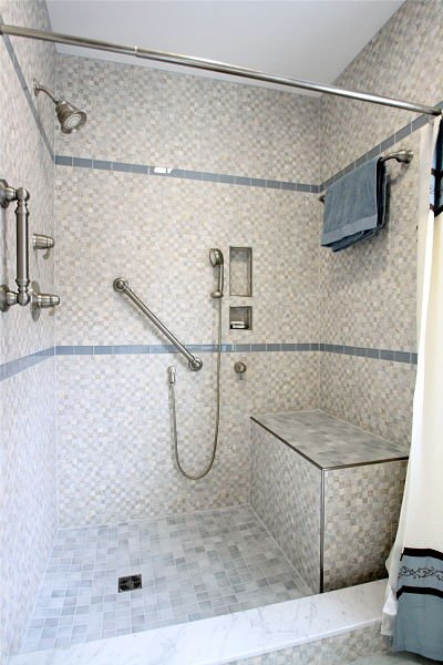 walk-in shower with grab bars and bench seat