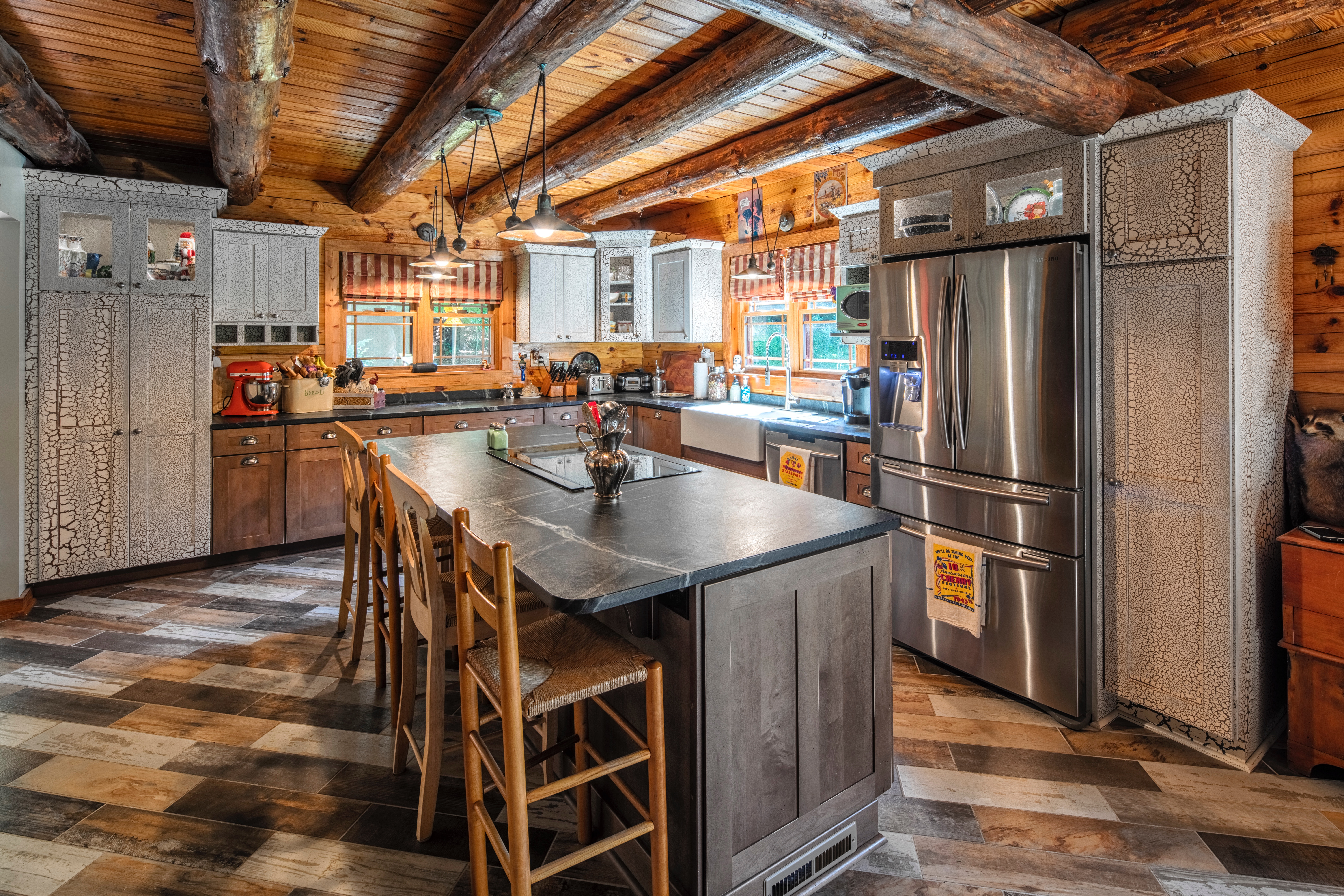 Custom speckled cabinets with multicolored wood grain floor tile. This kitchen brings an Adirondack cabin feeling to the best room in the house!