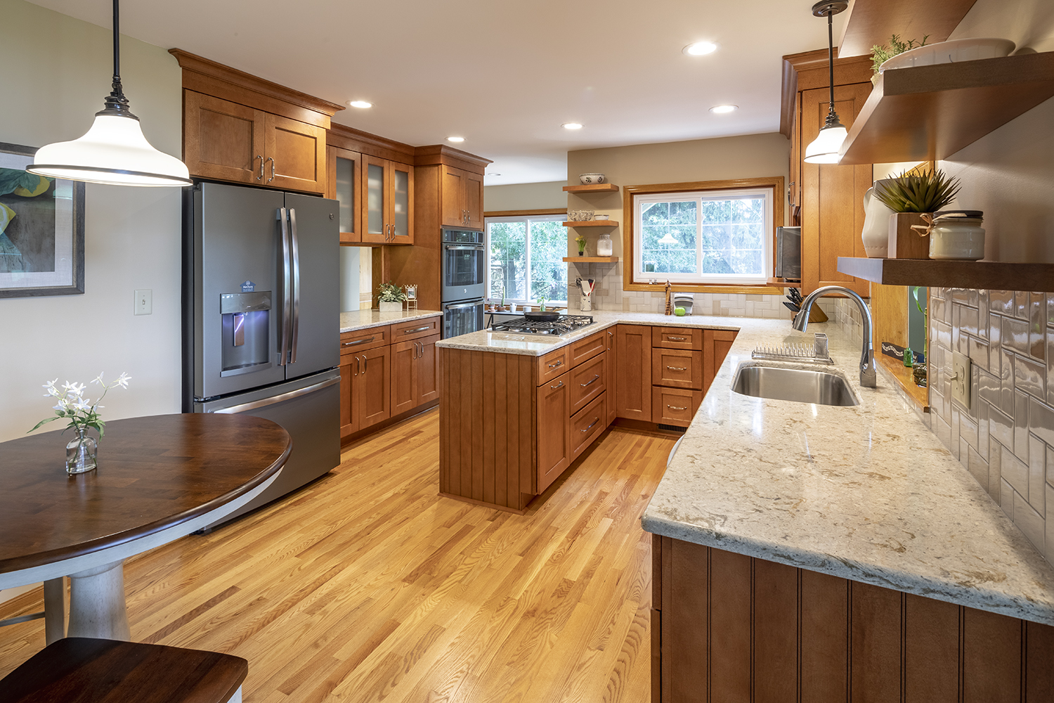 This kitchen was designed to save space, create open sight lines and bring in the nature light. This space captures access to the deck, sight lines to 2 other main living spaces, and the inclusion of a small sitting table.