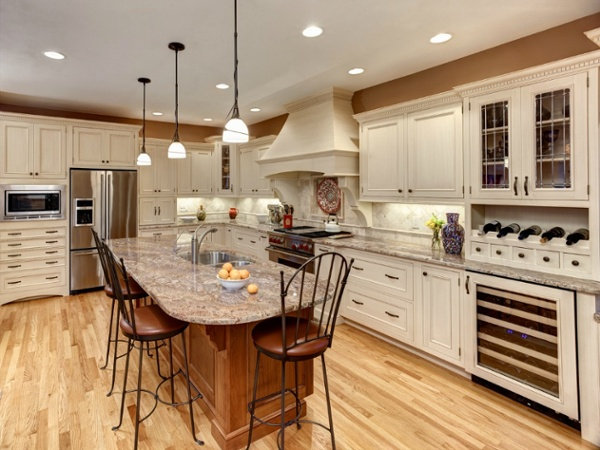 This L-shaped kitchen features custom cabinetry, a large island with dual stainless steel sink, commercial grade appliances and ample task lighting.