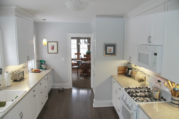 A galley kitchen was brought up-to-date and restored to reflect the original character of a home built in 1929 by adding white painted Shaker-style cabinets, white oak wood flooring, white appliances, a white cast-iron sink, laminate counters, tile backsplash and new lighting fixtures.