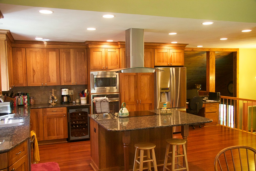 The new design of the kitchen includes a large central island to provide space for food prep, cooking, storage and the capacity to seat four to six people. An induction glass cooktop with a chimney-style vent hood was installed over the island.