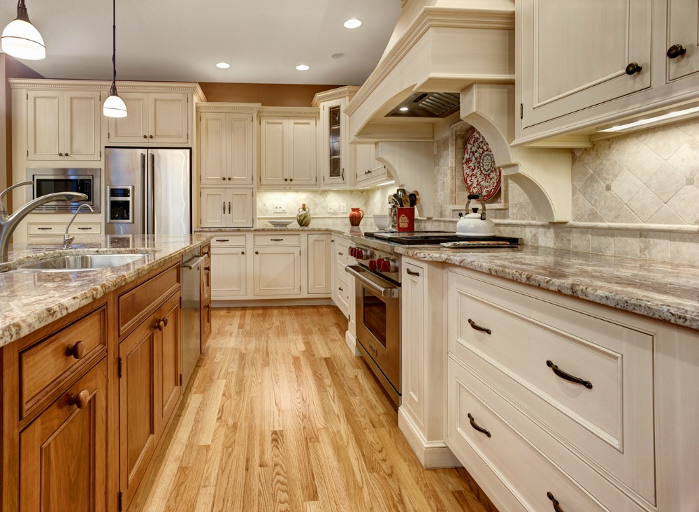 Charmant Granite Countertop With A Beveled Edge And Tumbled Marble Backsplash  Complement The White Painted Cabinetry.