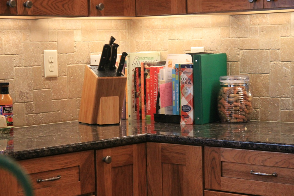 The Granite Countertop And Tumble Marble Backsplash Complement Wood Stained Cabinets