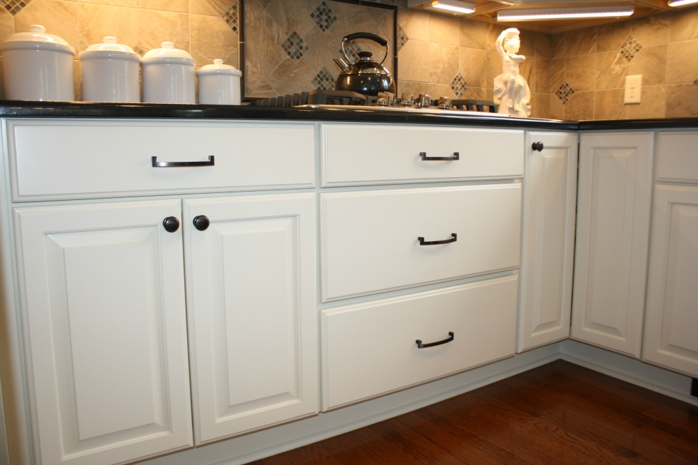 White Painted Cabinets Featuring Deep Storage Drawers And A Corner Carousel  That Make Storage More Accessible