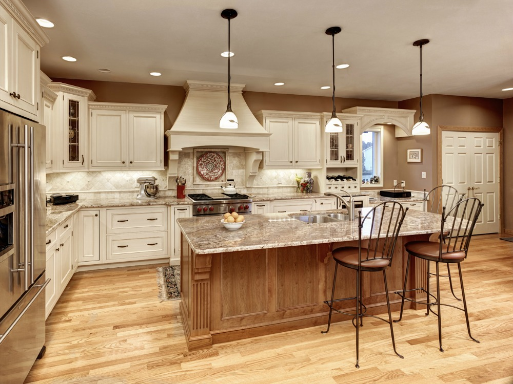 Three decorative pendant lights add interest to this elegant kitchen. The  white globes suspended from