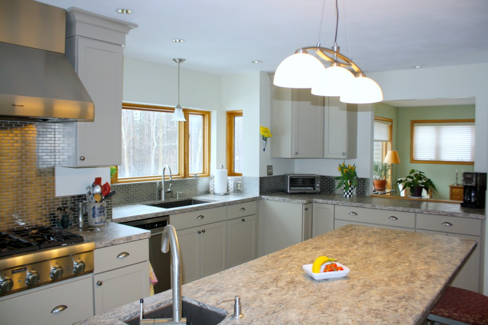 A three-lamp pendant fixture was place over the island. A matching pendant was selected to illuminate the main sink. Recessed lights were repositioned over work areas of the kitchen.