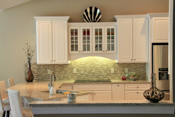 A glass marble mosaic tile backsplash complements the solid surface quartz countertop and provides an elegant updated look to the kitchen.