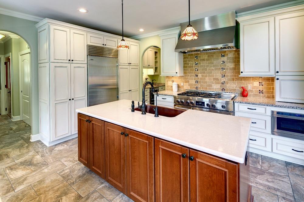 A subway tile backsplash complements the cabinets appliances flooring and fixtures copper accent