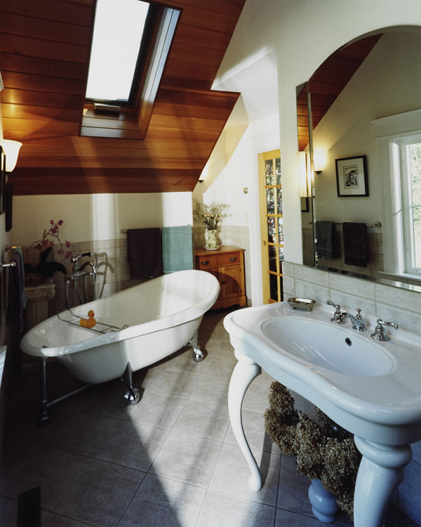 A tongue-and-groove cedar ceiling with skylight allows natural outdoor light to flow into this antique-style bathroom for a feeling of escape. The pedestal sink with arched mirror, and ceramic tile floor complement the design with simplicity and tranquility.