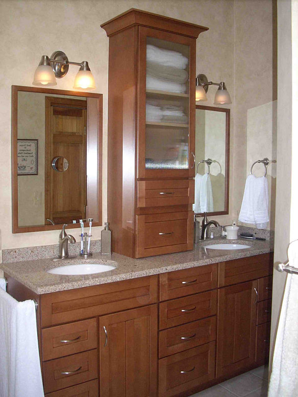 In this bathroom remodel, a storage tower provides space for towels and supplies and separates the dual sinks and framed mirrors. A stack of drawers separates the two base cabinets.