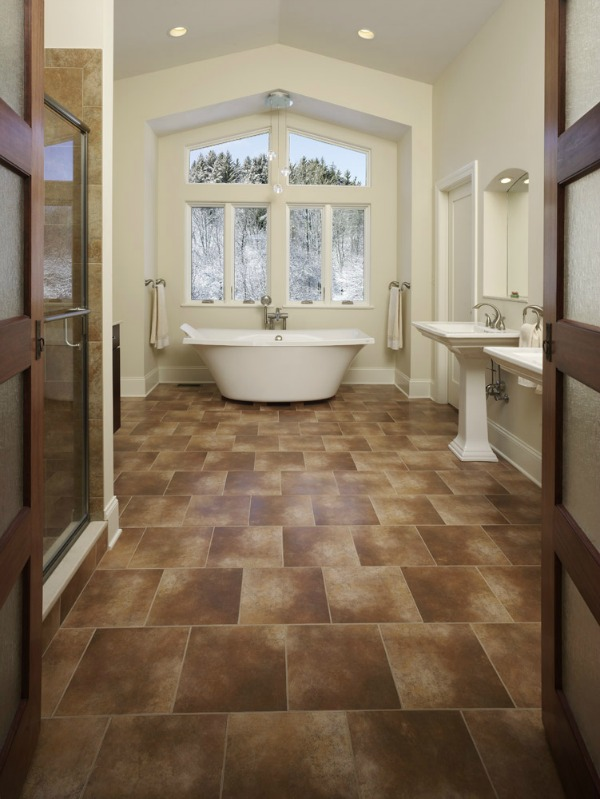 Cathedral ceilings, a wall of windows and large tile flooring make this showpiece bathroom appear large and spacious. The tub seems to be floating over the floor while large windows bring the outdoors inside.